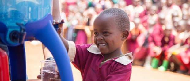 A pupil from Exodus Academy pours a glass of safe water from the new LifeStraw Community purifier, replacing dirty water from a local stream
