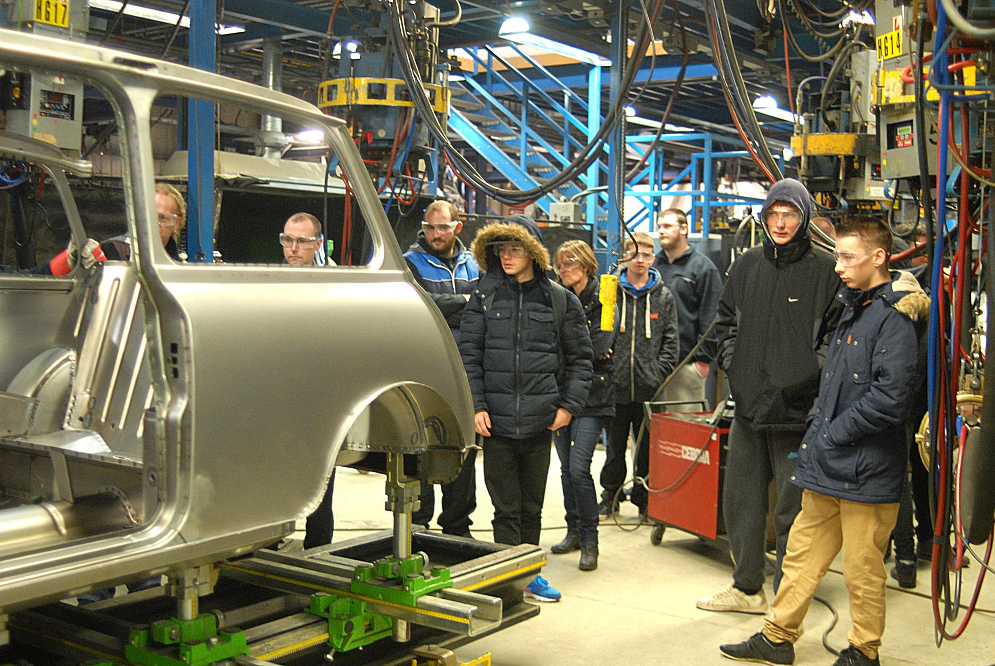 TRAX students look-on as a replacement classic Mini bodyshell takes place