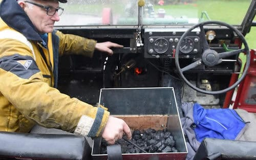 Frank Rothwell shoveling coal into his steam powered Land Rover