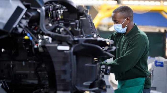 First Socially-Distanced Made Range Rover Roll Off The Line - Worker with mask working on line