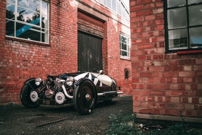 LIMITED-EDITION 3 WHEELER P101 - exterior photo against brick wall at Malvern factory